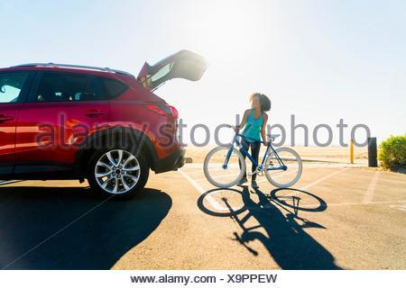 Mid adult woman putting location en car boot Banque D'Images