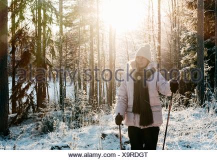 Mid adult woman marche nordique dans la forêt couverte de neige Banque D'Images
