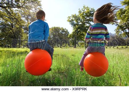 Les enfants sauter sur hoppity horses Banque D'Images