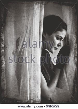 Side View of Young Woman Standing par des rideaux