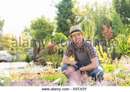 L'homme à la voiture tandis que les travaux de jardinage à la pépinière Banque D'Images
