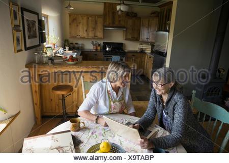 Les femmes âgées de rire en regardant l'album photo Banque D'Images