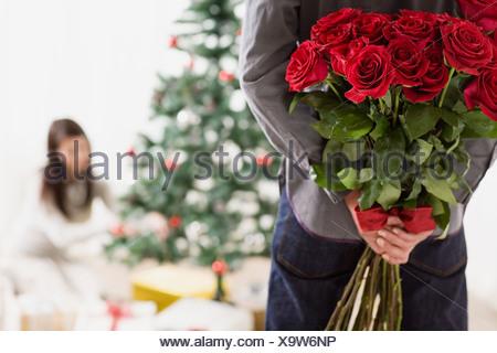 Homme tenant un cadeau surprise de roses Banque D'Images