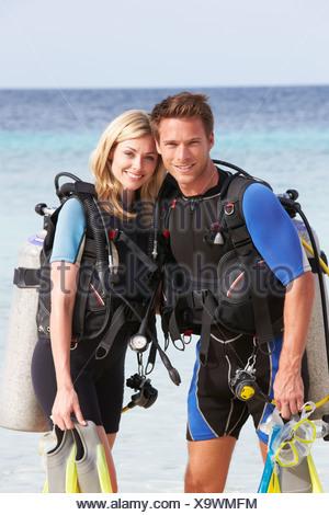 Couple avec équipement de plongée jouissant Plage Vacances Banque D'Images