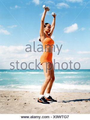 Femme brune, cheveux tressés portant un gilet orange rognée, orange  shorts, chaussettes blanches