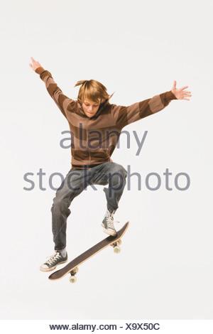 Teenage boy (13-14) performing jump sur planche, les bras Banque D'Images