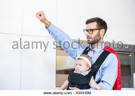 Père wearing superhero costume fille comptable Banque D'Images