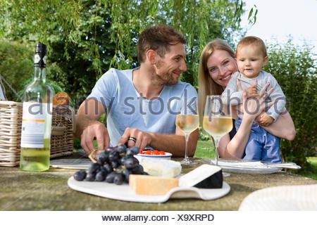Couple et sa petite fille assise à une table de pique-nique au jardin Banque D'Images