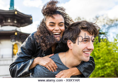 Young woman getting piggyback de copain dans Battersea Park Banque D'Images