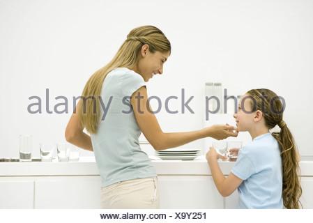 Mère et fille dans la cuisine, la femme tenant le menton de la jeune fille, smiling Banque D'Images