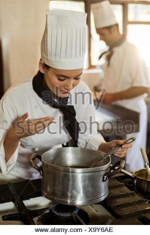 Smiling chef cuisinier en remuant dans cooking pot Banque D'Images
