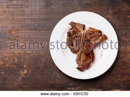 T-bone steak grillé sur plaque blanche sur fond de bois foncé Banque D'Images