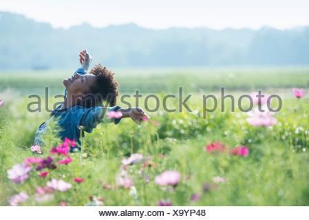 Une femme debout au milieu des fleurs avec ses bras tendus. Fleurs cosmos rose et blanc. Banque D'Images