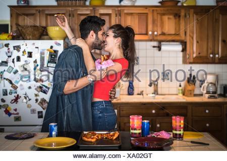 Jeune couple hugging in kitchen Banque D'Images