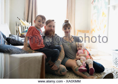Portrait young family relaxing in living room Banque D'Images