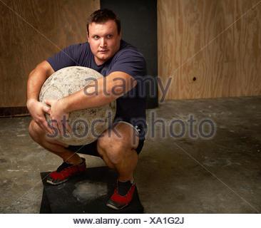 Portrait de jeune homme accroupi haltérophile avec atlas ball in gym Banque D'Images