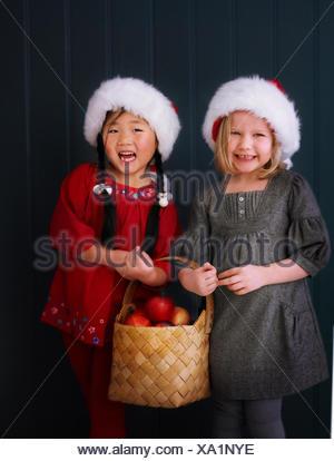 Suède, Stockholm deux filles wearing santa hats et holding basket aux pommes Banque D'Images