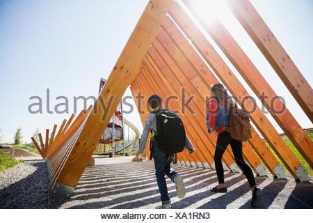 Les enfants de l'école avec des sacs d'exécution sous poutres de bois Banque D'Images