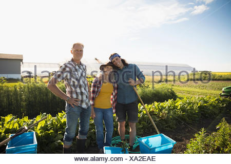 Portrait souriant, confiant les agriculteurs familiaux travaillant dans des cultures de légumes sur sunny farm Banque D'Images