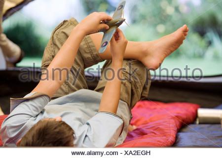 Boy 810 couché sur un sac de couchage à l'intérieur de tente sur jardin pelouse Playing with toy aero avion vue arrière Banque D'Images