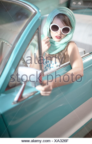 Femme au foulard et lunettes blanches en décapotable vintage Banque D'Images