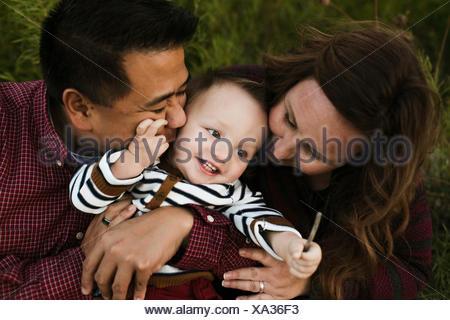 Mère et père hugging smiling baby boy Banque D'Images