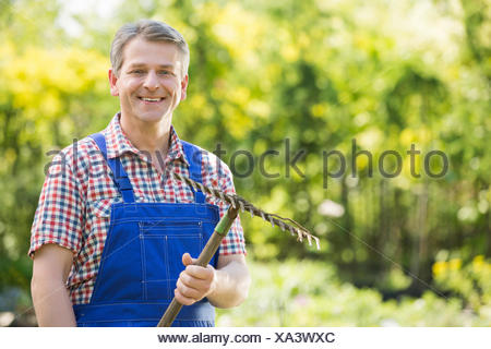 Portrait of smiling gardener holding rake in plant nursery Banque D'Images