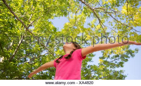 Une jeune fille aux tresses, vêtu d'un haut rose avec ses bras tendus et la tête en arrière.