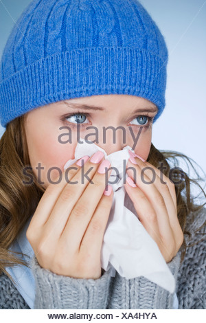 Une jeune femme s'être mouché le nez, close-up Banque D'Images