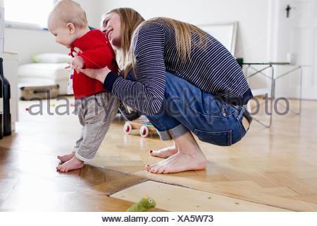 Mid adult woman holding baby fille de prendre des premières mesures Banque D'Images