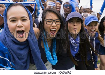Portrait des femmes enthousiastes acclamations événement sportif en bleu Banque D'Images