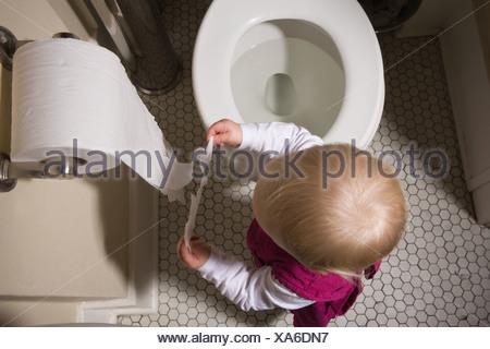 Petite fille de déchirer le papier de toilette Banque D'Images