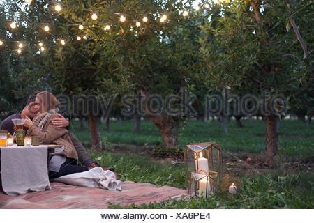 Apple orchard. Couple assis sur le sol Banque D'Images