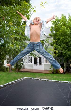 Garçon sautant sur le trampoline Banque D'Images