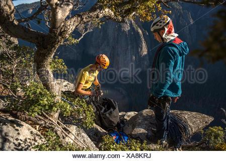 Deux hommes l'escalade libre un grand mur itinéraire sur El Capitan dans le Parc National de Yosemite Prk dans les montagnes de la Sierra Nevada, en Californie. Banque D'Images