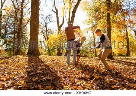 Jeune femme playfighting avec deux jeunes frères en forêt d'automne Banque D'Images