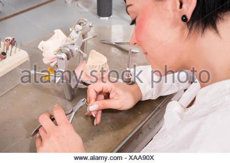 Zahntechnikerin dans un laboratoire dentaire dentiers avec Banque D'Images