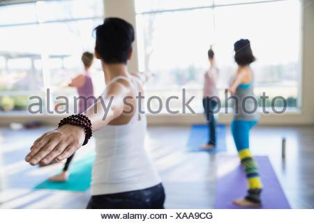 Les femmes pratiquant guerrier 2 poser dans la classe de yoga Banque D'Images