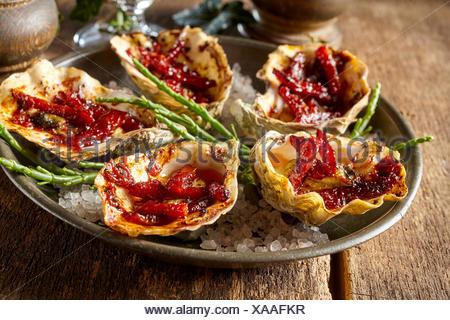 Close Up Portrait of Plate of Kilpatrick huîtres préparées avec du bacon et du fromage et servi sur une table en bois rustique avec du sel et garnir vert Banque D'Images