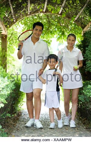 Un enfant une famille va jouer au tennis Banque D'Images