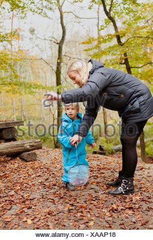 Mère d'aider son fils à jouer au badminton Banque D'Images