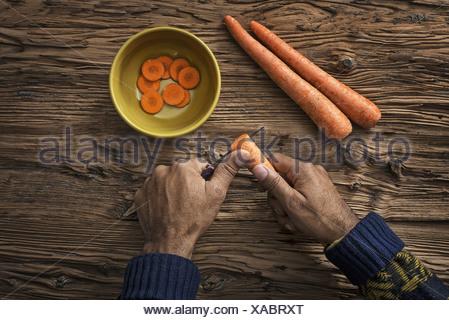 Une personne tenant et découpage des carottes fraîches dans un bol Banque D'Images