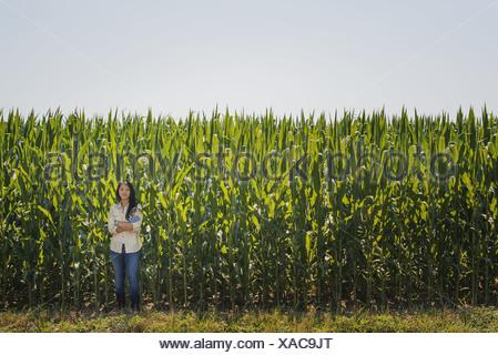 L'état de New York États-unis Jeune femme debout bras croisés récolte de maïs maïs Banque D'Images
