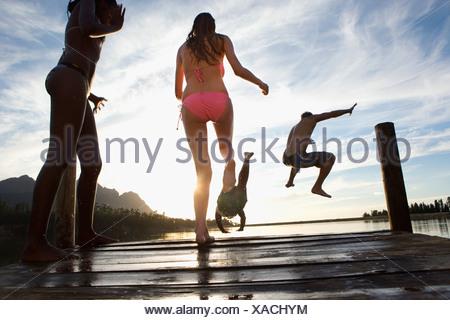 Quatre jeunes adultes en sautant de maillots jetty dans le lac au coucher du soleil Vue arrière avec la surface Banque D'Images