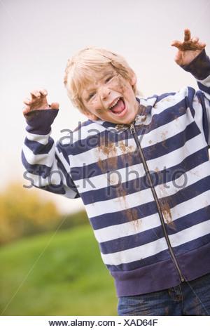 Jeune garçon debout à l'extérieur sale et smiling Banque D'Images