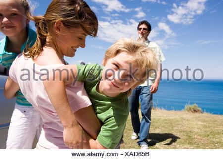 Mère embrassant son fils et sa fille 79 sur falaise dominant l'océan Atlantique à la recherche de père Banque D'Images