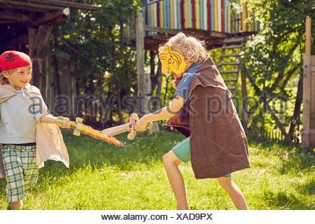 Deux jeunes frères en jardin, portant des costumes et jouant avec prétendre swords Banque D'Images