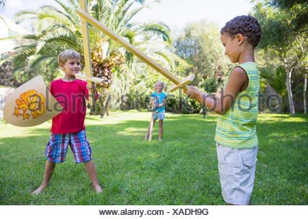 Trois enfants en jardin Playing with toy swords Banque D'Images