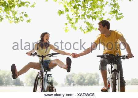 Heureux couple riding bicycles and holding hands Banque D'Images