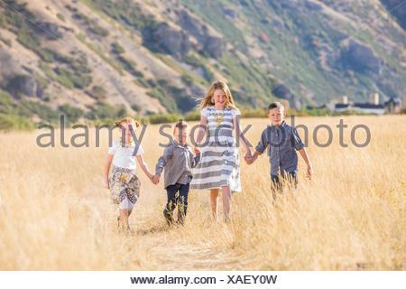 USA, Utah, Provo, les garçons et les filles (4-5, 6-7, 8-9) walking in field, holding hands Banque D'Images